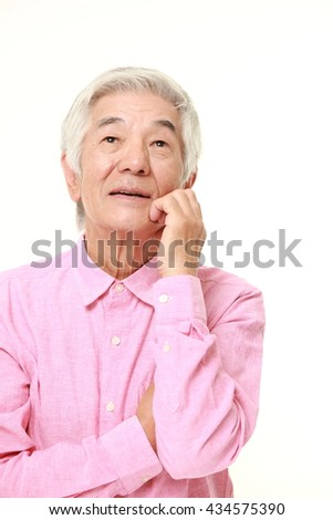 senior Japanese man in a pink shirts thinks about something - stock photo