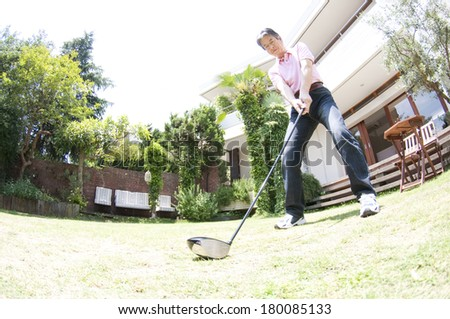Senior Japanese man practicing golf in the backyard