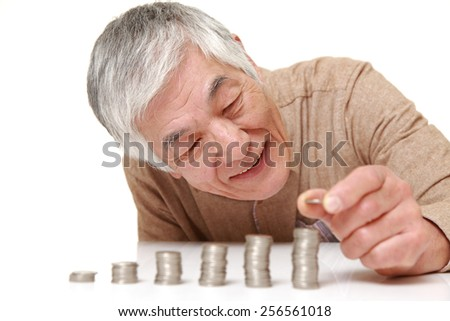 senior Japanese man put coins to stack of coins - stock photo