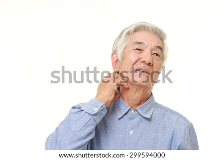 senior Japanese man scratching his neck - stock photo