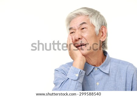 senior Japanese man suffers from toothache - stock photo