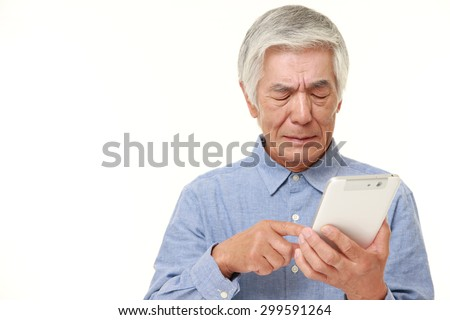 senior Japanese man using tablet computer looking confused - stock photo