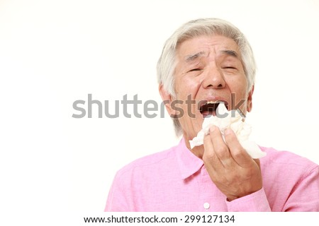 senior Japanese man with an allergy sneezing into tissue - stock photo