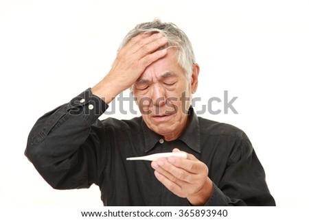 senior Japanese man with fever - stock photo