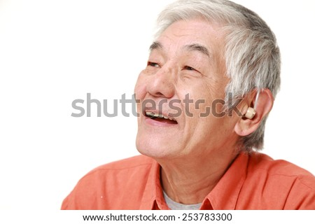 senior Japanese man with hearing aid - stock photo