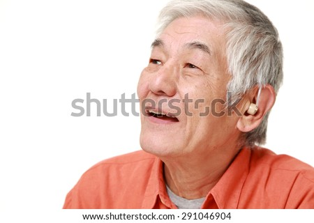 senior Japanese man with hearing aid - stock photo