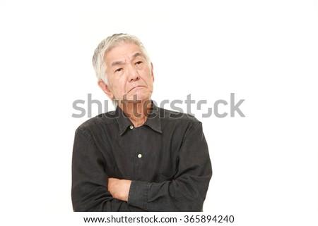 senior Japanese man worries about something - stock photo