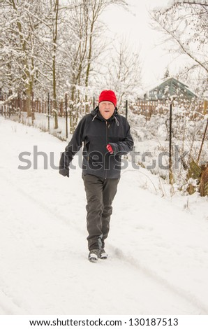 Senior jogging in winter as warm-up before cross country skiing