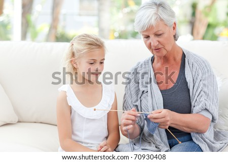 Senior knitting with her granddaughter at home