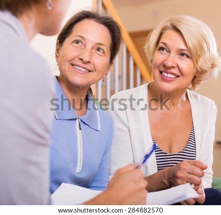 Senior ladies signing documents with agent and smiling at home - stock photo