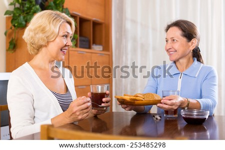 Senior ladies with cups of tea and pastry at home.Focus on the woman on the left - stock photo