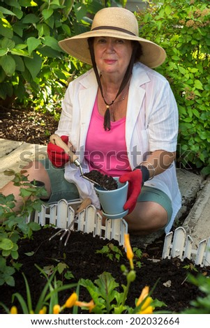 Senior lady doing yard work around the house sitting on the paving stones in the garden potting up a plant in a flowerpot and smiling at the camera