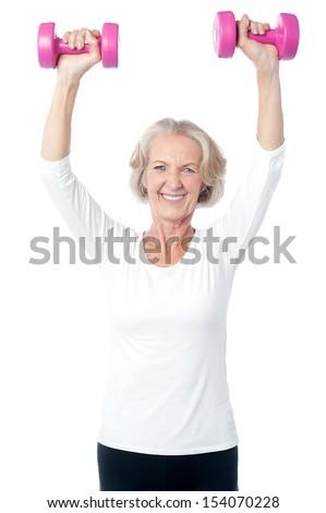 Senior lady exercising happily with dumbbells - stock photo