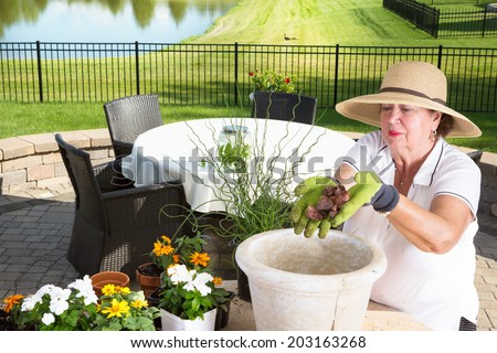 Senior lady gardener potting up a large planter on an outdoor brick patio adding a handful of stones to the bottom for drainage and aeration before adding the plants and soil - stock photo