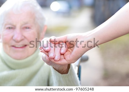 Senior Lady in Wheelchair and Young Woman Holding Hands Outside - stock photo