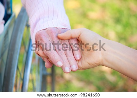 Senior Lady in Wheelchair Holding Hands with a Young Caretaker or Loved-one - stock photo
