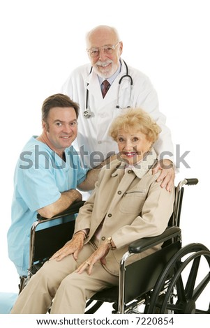 Senior lady in wheelchair with her doctor and nurse.  Isolated on white. - stock photo