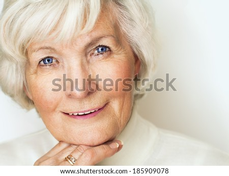 Senior lady looking relaxed and smiling at camera - stock photo