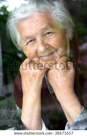 Senior lady looking through window and smiles - stock photo
