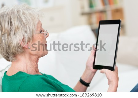 Senior lady relaxing at home on a sofa reading an e-book on her tablet, over the shoulder view with the blank screen visible - stock photo