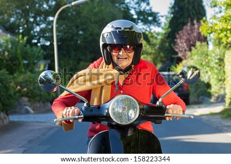 Senior lady riding a scooter. Senior lady wearing a helmet, sunglasses and a scarf riding her scooter directly at the camera with a wide smile of pleasure - stock photo
