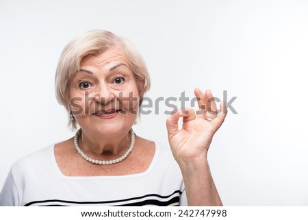 Senior lady satisfied. Closeup portrait of active elderly woman smiling and showing OK sign while standing against white background - stock photo