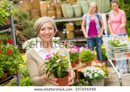 Senior lady shopping for flowers at garden centre smiling