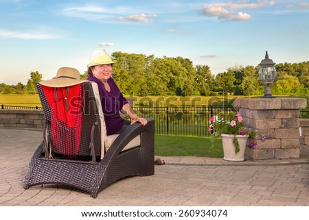 Senior lady sitting in a modern comfortable wicker armchair overlooking a tranquil lake and lush green countryside watching the sunset from an outdoor patio turning to look round at the camera - stock photo