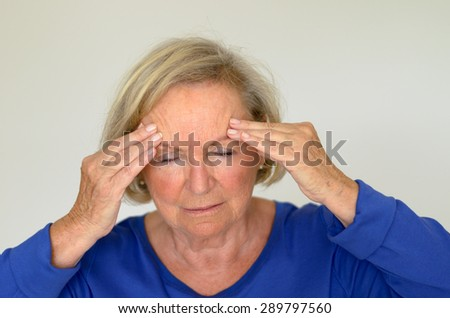 Senior lady suffering with a headache or fever holding her hand to her forehead with her eyes closed in pain, head and shoulders over gray - stock photo