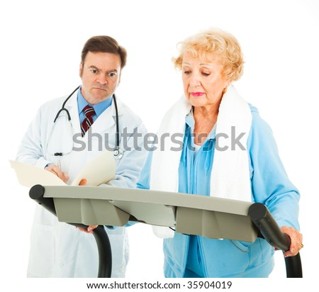 Senior lady walks on treadmill under the supervision of her doctor.  Isolated on white. - stock photo