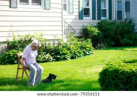 Senior lady with her dog relaxing in front yard