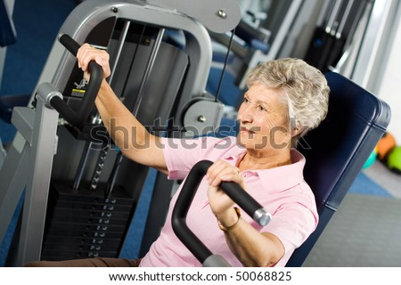 Senior lady working out at the gym - stock photo