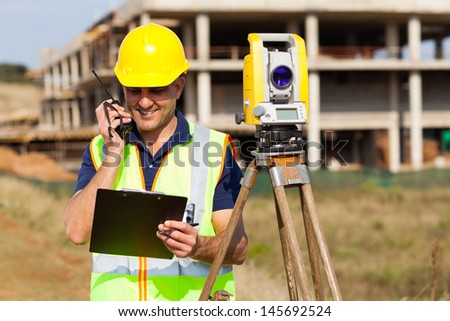 senior land surveyor talking on walkie talkie - stock photo