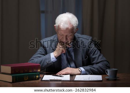 Senior lawyer working overtime in law firm - stock photo