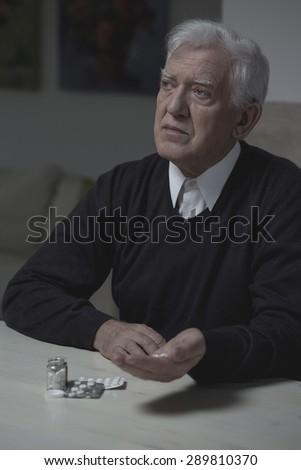 Senior lonely man taking medicament for depression - stock photo