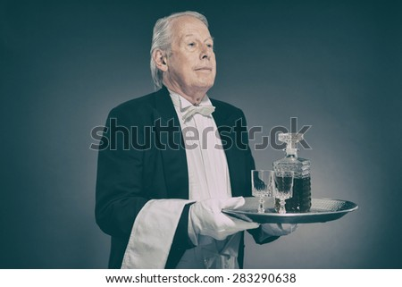 Senior Male Butler Wearing Tuxedo and Serving from Tray with Liquor Bottle and Crystal Cordial Glasses - stock photo