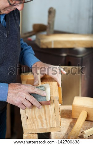 Senior male carpenter using sandpaper for polishing birdhouse at worktable in workshop - stock photo