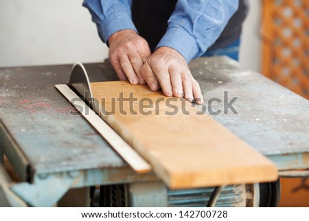 Senior male carpenter using table saw for cutting wood at workshop - stock photo