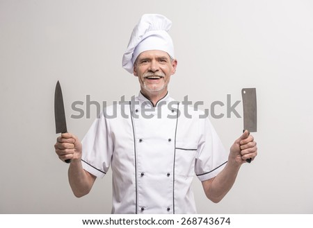 Senior male chief cook in uniform holding knifes a  on grey background. - stock photo