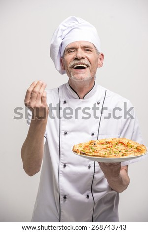 Senior male chief cook in uniform holding pizza on grey background.