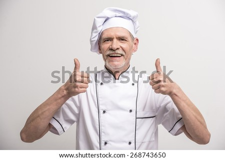 Senior male chief cook in uniform showing thumb up on grey background. - stock photo