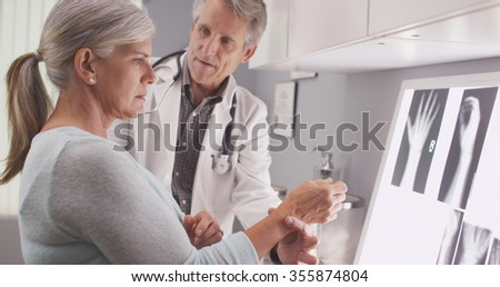 Senior male doctor assessing patient's fractured wrist - stock photo