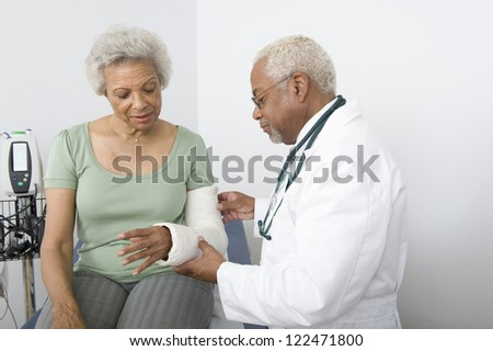 """Senior male doctor checking patient""""s fractured hand - stock photo"""