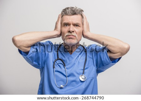Senior male doctor holding a head on grey background. - stock photo