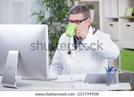 senior male doctor in the office working on the computer - stock photo
