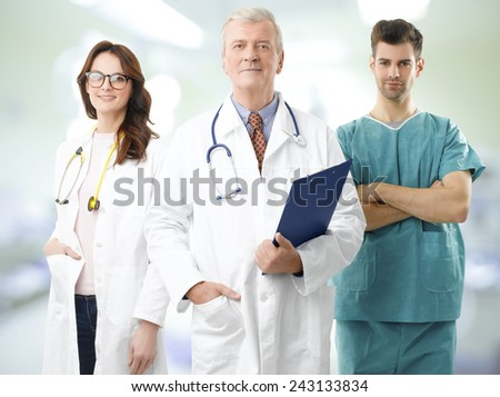Senior male doctor standing at private clinic and holding medical chart while his medical team at background. - stock photo