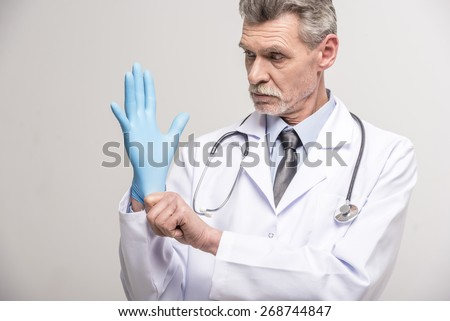 Senior male doctor wearing glove on grey background.