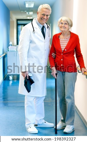 Senior male doctor with an elderly woman patient at the hospital standing together in the passage supporting her by the arm as she walks with a cane  both smiling happily at the camera.