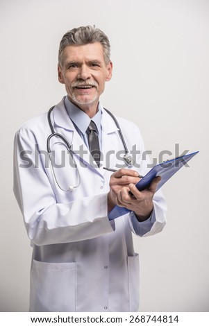 Senior male doctor writing a prescription on grey background. - stock photo
