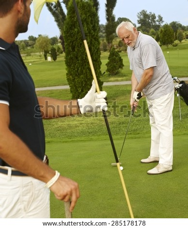 Senior male golfer holing, young man holding flag. - stock photo